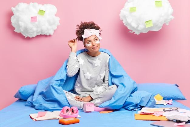 소녀는 잠옷을 입고 곱슬 머리는 창의적인 프로젝트를 만드는 것에 대해 생각하며 침대에 머물며 눈 아래에 미용 패치를 적용합니다.