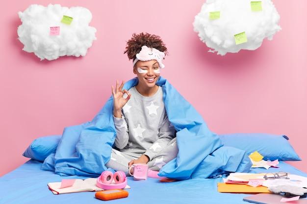 女の子は寝間着を着ている ほほえむ 広く笑う 大丈夫 ジェスチャー 優れたジェスチャー ウィンク 目のポーズ 快適なベッドで組んだ足 書類に囲まれた ノート ステッカー