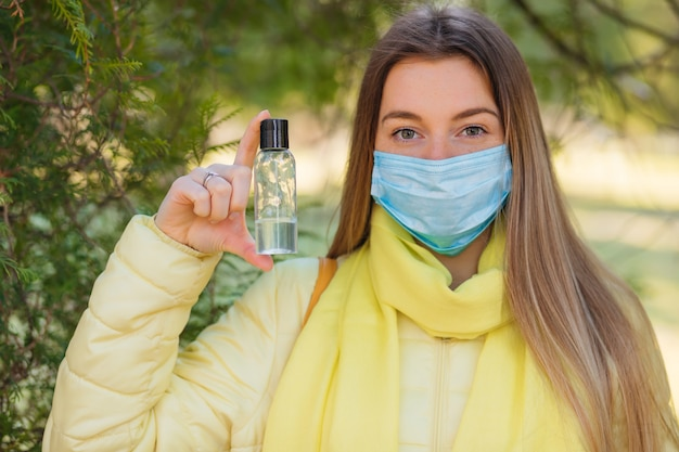 Girl wears a protective mask and holds bottle of alcohol antiseptic gel,equipment for disinfection,pandemic of covid-19,coronavirus outbreak,hand sanitizer to protect against contagious disease