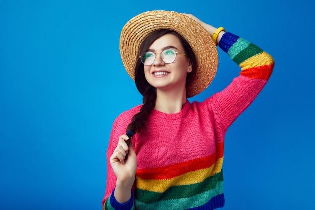 Девушка в радужном свитере и летней соломенной шляпе улыбается и смотрит в сторону