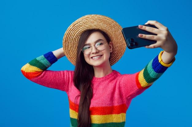 Девушка в радужном свитере делает селфи на мобильный и широко улыбается