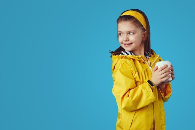 Девушка в плаще держит чашку с чаем на вынос и смотрит на свободное пространство