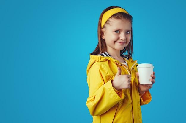 Девушка в плаще держит чашку с чаем на вынос и показывает палец вверх