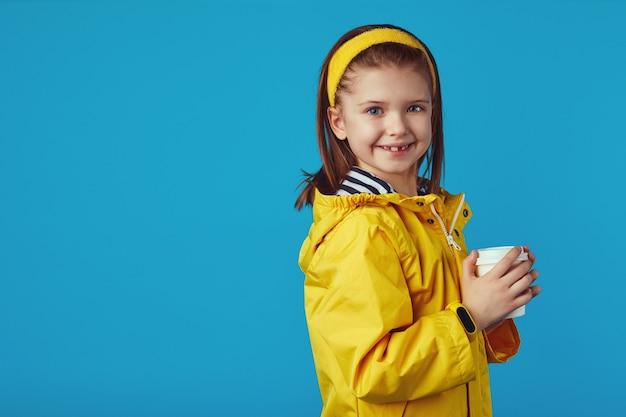 Девушка в плаще держит чашку с чаем на вынос и улыбается на синем фоне