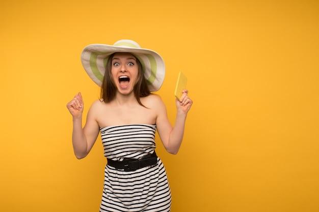女の子はスマートフォンで麦わら帽子と開いた肩の幸せなニュースで短い白いストリップドレスを着ています