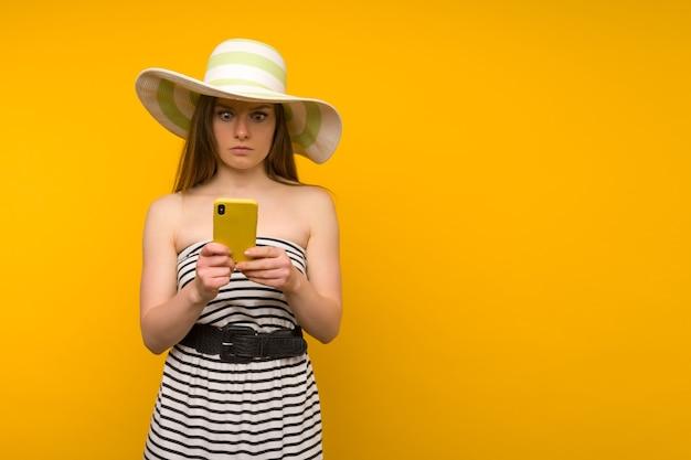 女の子はスマートフォンのニュースに驚いた麦わら帽子と開いた肩の短い白いストリップドレスを着ています
