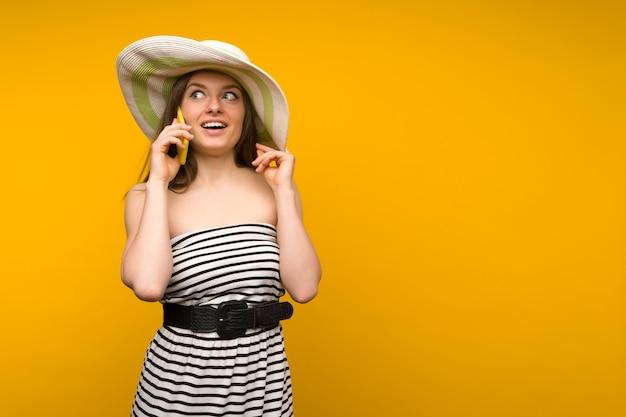 女の子はスマートフォンで話している開いた肩と麦わら帽子と短い白いストリップドレスを着ています