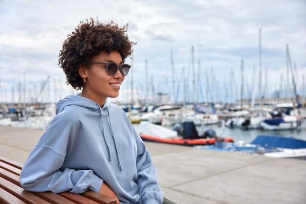 女の子はサングラスをかけ、パーカーは日中の港の散歩でヨットやセーリングのポーズを楽しんでいます贅沢な旅行があります