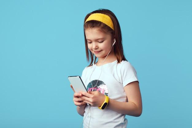 Девушка в белой рубашке слушает музыку в наушниках и держит смартфон