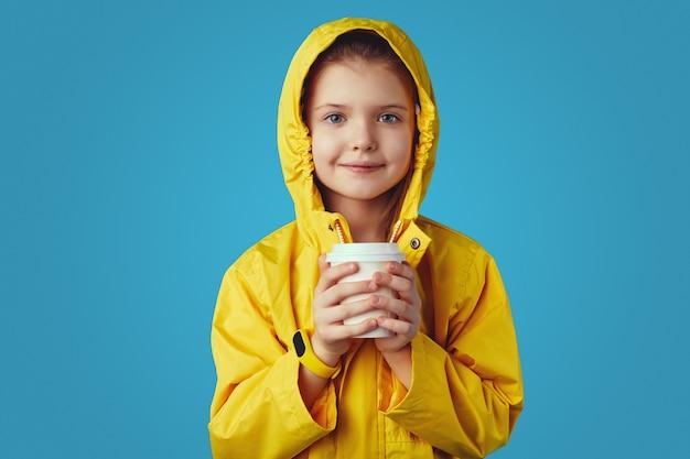 Девушка в желтом плаще держит чашку с чаем, пытается согреться, пока пьет