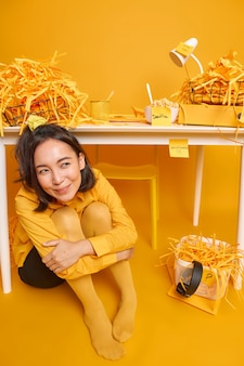 Girl wears yellow shirt and tights feels glad after finishing important task poses indoor near office desk has much paper wastes around thinks about something pleasant