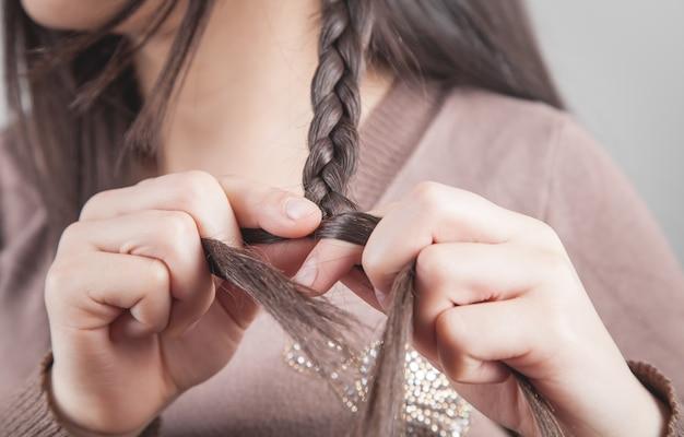 三つ編みに髪を編む少女。