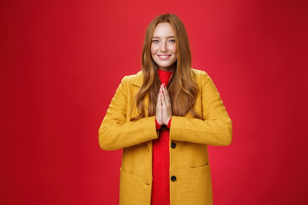 Girl welcomes us with buddhist namaste gesture pressing palms together over chest smiling friendly and delighted with carefree emotions holding hands in pray, posing happily over red background.