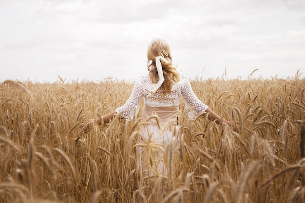 Girl in a wheat field in summer. back view