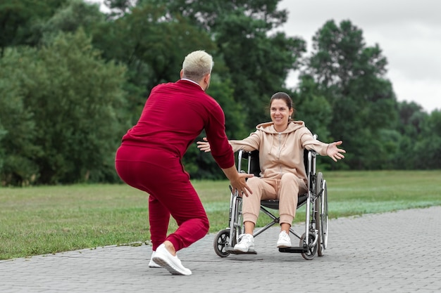 A girl on a wheelchair with a man spend time in the park. the young woman is disabled. the concept of a wheelchair, disabled person, full life, paralyzed, disabled person, health care.