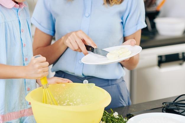 그녀의 어머니가 부드러운 버터를 추가 할 때 그릇에 반죽을 털어내는 소녀