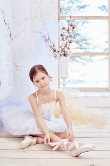 Girl in a white ball gown and pointe near the window