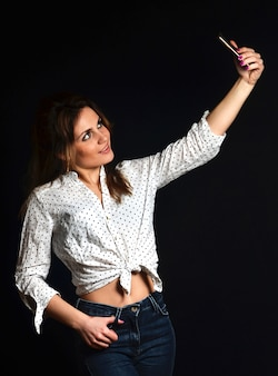 Girl in white blouse and jeans makes selfie on smartphone on black background.