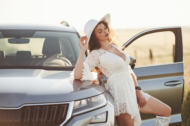 Girl in white clothes posing near the modern luxury automobile outdoors