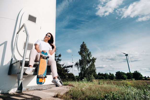 A girl in white clothes with a skate in her hands is photographed near large wind turbines in a field with trees.modern woman with a board for riding in a field with windmills.