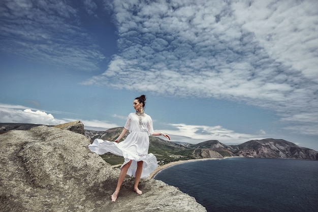 A girl in a white dress and decorations stands on a cliff