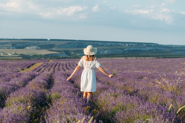 A girl in a white dress and a hat with bouquets in her hands stands back in a lavender field