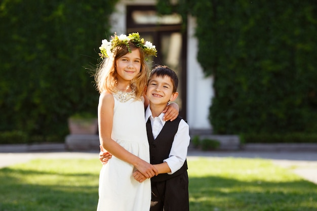 A girl in a white dress hugs a boy in a fashionable suit.