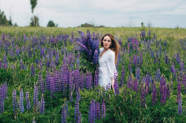 A girl in a white dress is standing among the lupines