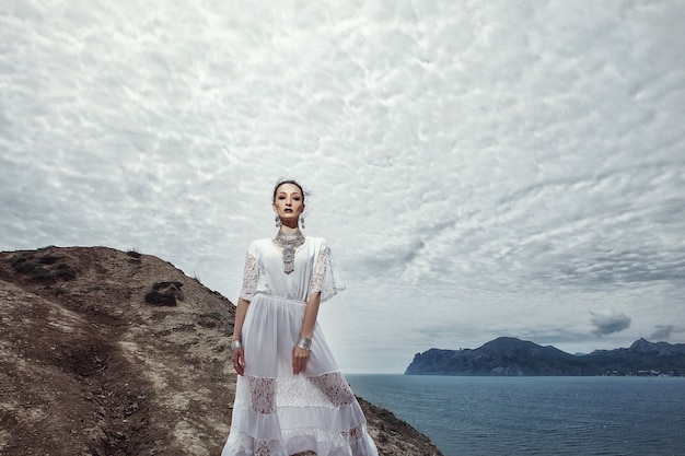 A girl in a white dress and jewelry stands on a cliff