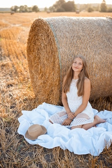Girl in a white dress near the bale of straw on the white cloth on the agricultural field in the evening