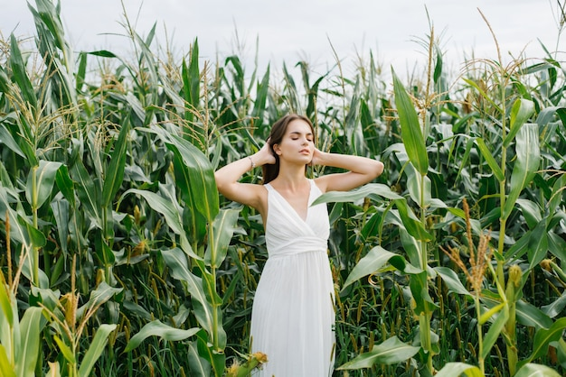 Girl in white dress standing in a corn field