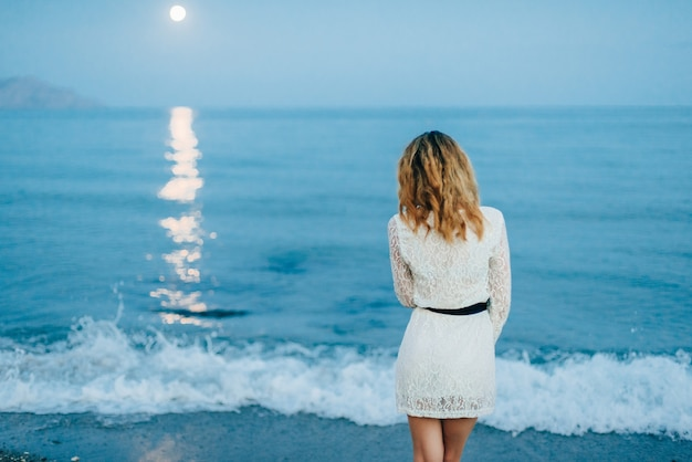 Girl in a white dress stands with her back on beach by sea
