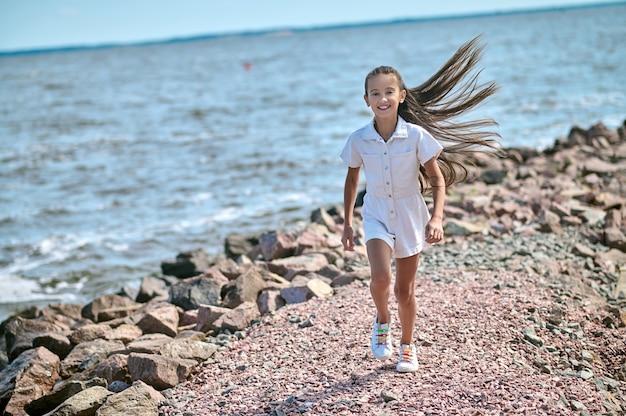A girl in a white dress walking on a beach