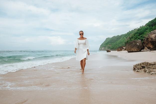 Girl in white dress walking on white beach