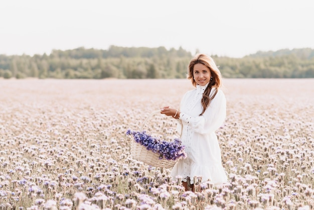 Girl in a white dress with a bouquet of flowers in a basket