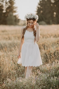Girl in white dress with floral wreath and braids in summer field