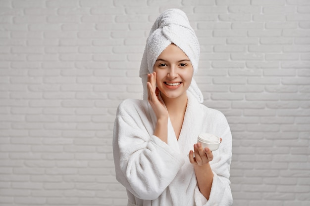 Girl in white dressing gown and towel caring about skin