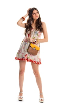 Girl in white floral dress. brown and orange bag. sandals and flax garment. summer clothes of stylish design.