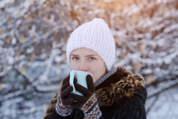 Girl in a white hat with a cup of tea among the snow-covered tree branches