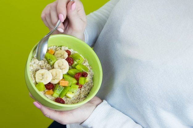 A girl in white holds a plate of oatmeal with fruit. top view