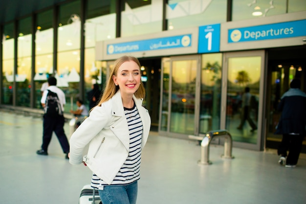Girl in white jacket and stripped shirt walks with suitcase from airport