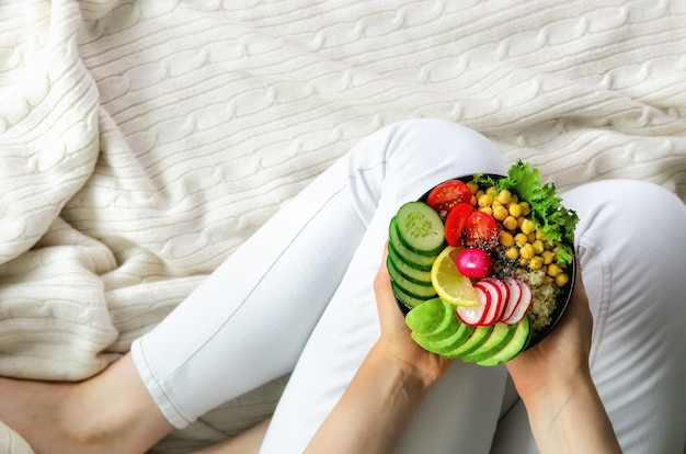 Girl in white jeans holds in hands fork, vegan breakfast meal in bowl with avocado, quinoa, cucumber, radish, salad, lemon, cherry tomatoes, chickpea