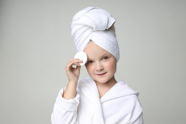 Girl in a white robe and a towel on her head after a shower and washing her hair. children cosmetics and skin care, spa treatments.