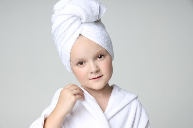 Girl in a white robe and a towel on her head after a shower and washing her hair.