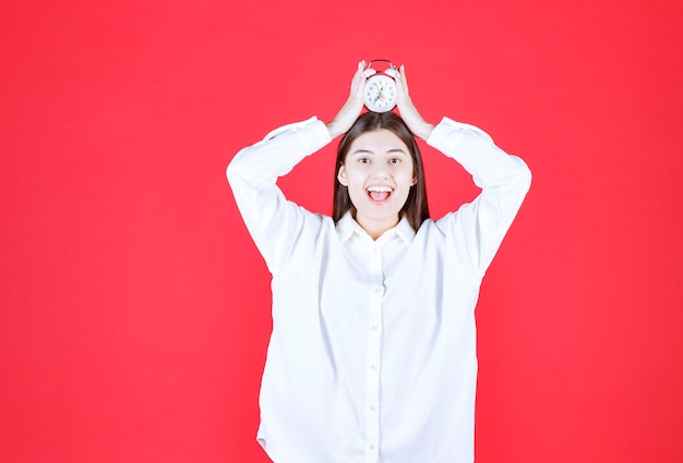 Girl in white shirt holding an alarm clock over her head and looks excited