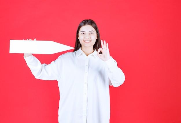 Ragazza in camicia bianca che tiene una freccia che punta a destra e mostra il segno della mano ok