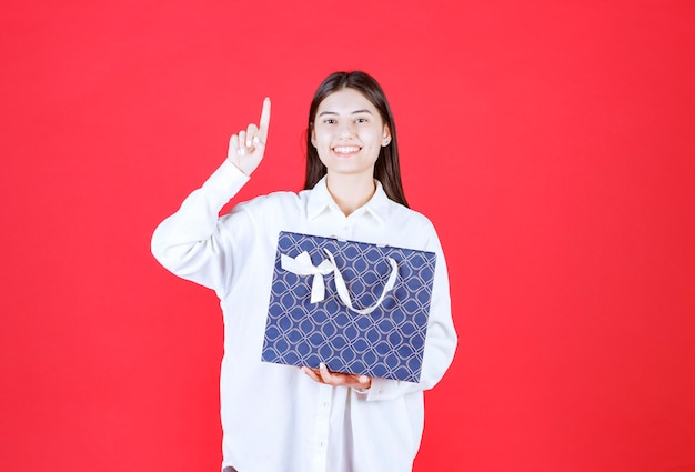 Ragazza in camicia bianca con in mano una borsa della spesa blu e sembra confusa e pensierosa