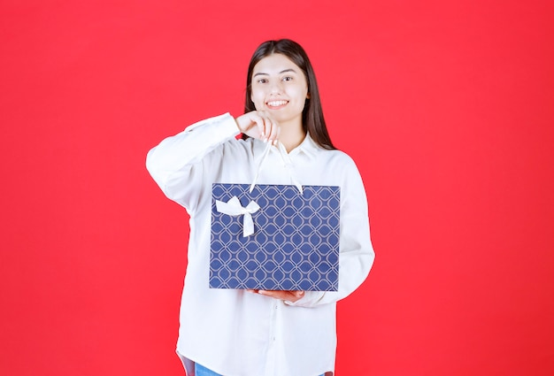 Ragazza in camicia bianca con in mano una borsa della spesa blu