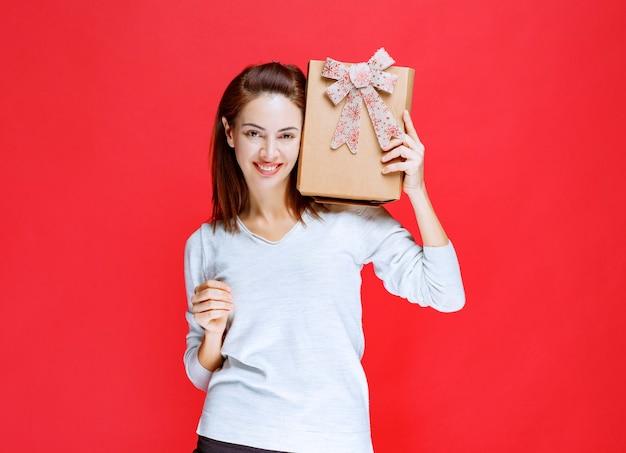 Ragazza in camicia bianca che tiene in mano una scatola regalo di cartone e mostra un segno positivo con la mano