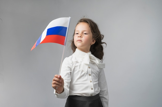 Girl in a white shirt holding the flag of the russian federation